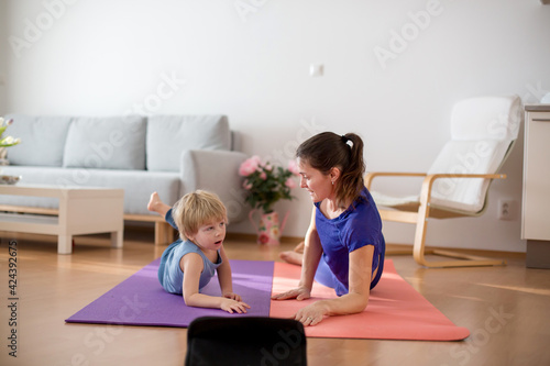 Obraz Mother and children, exercising at home during coronavirus, people making gymnastic at home - fototapety do salonu