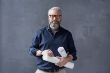 Portrait Of Mature Bearded Architect In Eyeglasses Standing With Blueprints Against The Black Background