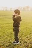 Little boy stay in a green wheat field in sunset