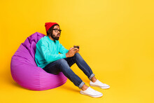 Full Size Profile Photo Of Brunette Optimistic Guy Playstation Wear Cap Spectacles Pullover Jeans Isolated On Yellow Background