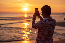 Silhouette Of Happy Young Man Taking Photo By Smartphone.Tourist Enjoy Beautiful Sunset At The Beach. Travel, Relaxing, Vacation Summer Concept