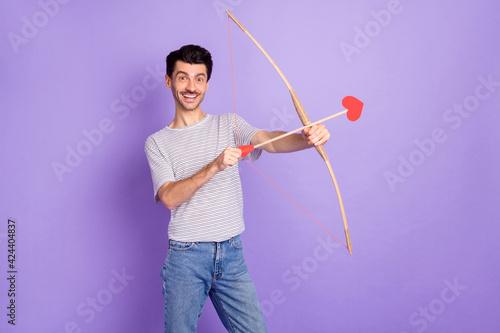 Photo of crazy cherub guy hold bow arrows aim shot shiny smile wear white t-shir Fotobehang