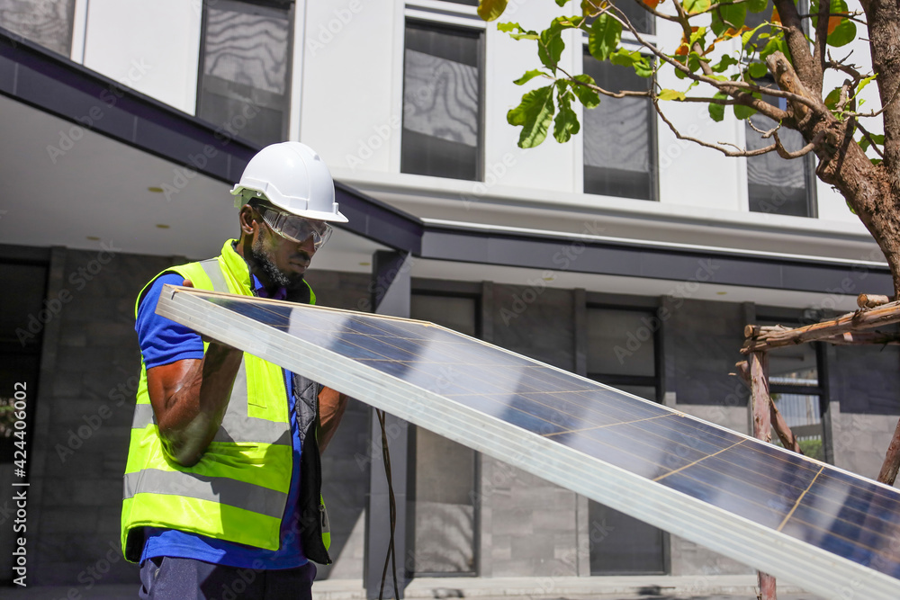 Fototapeta African American worker working on installing solar panel on the rooftop of the house for renewable energy and environmental friendly outcome concept