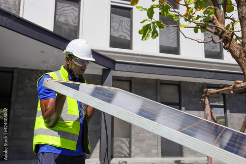 Obraz African American worker working on installing solar panel on the rooftop of the house for renewable energy and environmental friendly outcome concept - fototapety do salonu