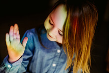 Rainbow Reflection On The Face And Hand Of The Child