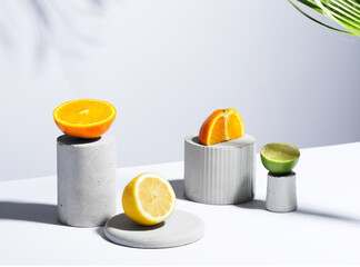 Citrus still life concept with lemon,lime and orange on gray stands and podiums over white background, horizontal