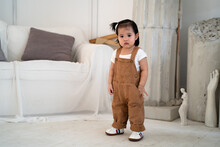 Portrait Of Asian Baby Infant In Brown Standing In White Artis Drawing Room Near Sofa Couch.