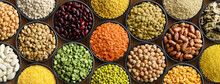 Various Colorful Legumes And Cereals In Black Bowls Background.