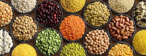 Foto Various colorful legumes and cereals in black bowls background.
