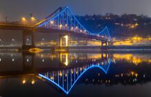 Pedestrian Bridge In Kiev. Evening Lighting. Reflection Of The Bridge In The River.