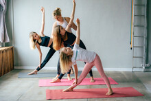 Taking Care Of Your Body, Morning Exercises And Stretching. The Girls Do Yoga Poses Under The Supervision Of Their Mother. Sports Healthy Discipline. Youth Training, Relaxing Practice, Morning Workout