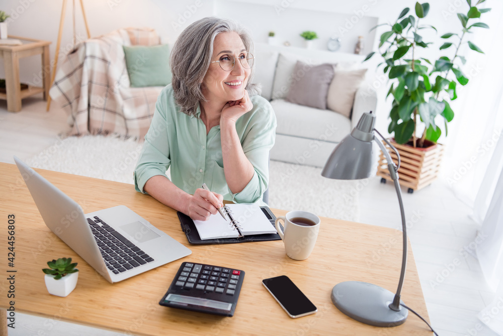 Fototapeta Portrait of charming cheerful person sit behind desktop hand on chin look interested tv working from home indoors