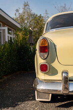 Close Up Of Taillight Of A Vintage Car Parked In A Sunny Front Yard.