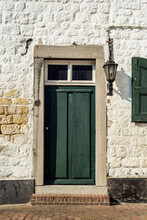 Old White Stone Wall With A Green Front Door And A Lantern.