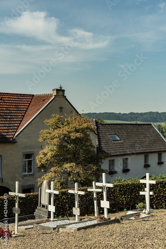 Cemetery with white wooden crosses under blue cloudy sky. Wall mural