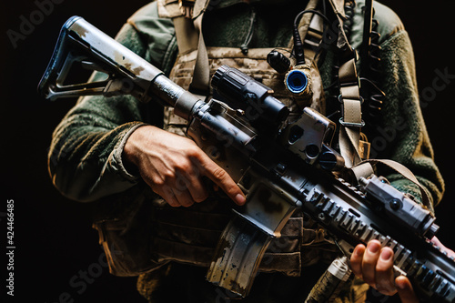 Fototapeta Unrecognizable special forces soldier standing with rifle against black dark bac