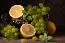 Still Life With Grapes, Lemon And A Tin Vase On A Brown Stone Background. Dutch Still Life. Dark Photo