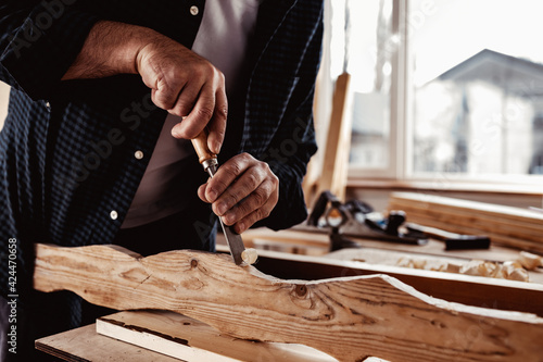 Fototapeta Hands of a carpenter working with chisel and hammer