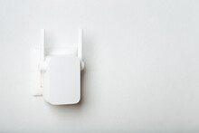 White Wi-fi Repeater Indoors At Home In Outlet. Wireless Router