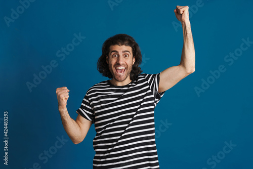 Foto Excited brunette man in t-shirt exclaiming and making winner gesture