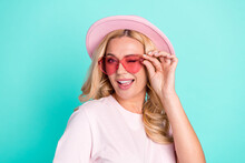 Portrait Of Attractive Cheerful Wavy-haired Woman Wearing Pink Hat Touching Specs Winking Isolated On Bright Green Turquoise Color Background