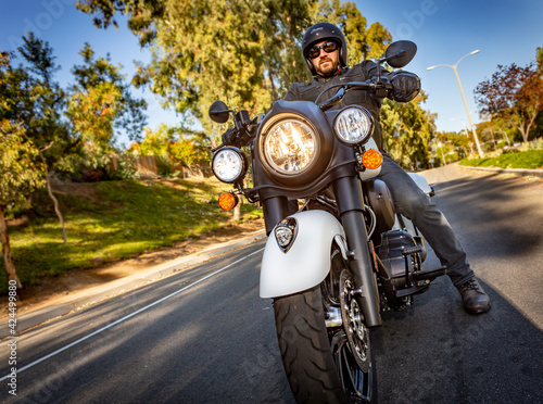 Fototapeta Low angle image of a motorcyclist dressed in leather