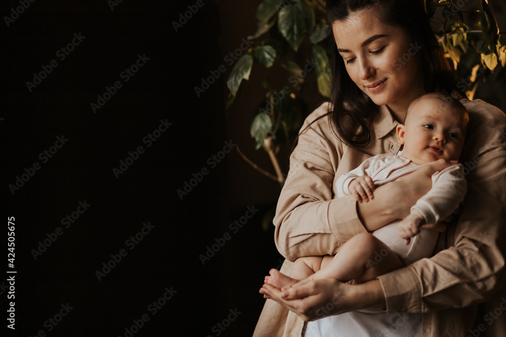 Fotografia Loving mom carying of her newborn baby at home in evening