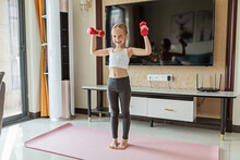 Little Girl In Sport Clothing Exercising At Home. Online Training During Coronavirus Covid-19 Quarantine. Stay Fit And Safe During Pandemic Lockdown. Sport, Fitness, Healthy Concept