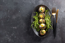 Baked Champignons With Quail Eggs And Microgreen Garnish On A Black Plate Close Up Top View, Photo With Free Space For Text