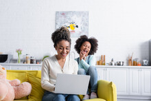 Excited African American Girl Laughing Near Mother Working On Laptop At Home