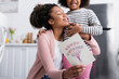 canvas print picture cheerful african american woman showing happy mothers day card while hugging daughter in kitchen, blurred background