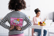 canvas print picture back view of african american child holding happy mothers day card near mom working in kitchen on blurred background