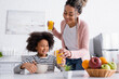 canvas print picture smiling african american woman giving orange juice to daughter near fruits on blurred foreground