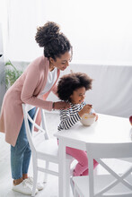 Smiling African American Woman Touching Shoulders Of Daughter Having Breakfast In Kitchen