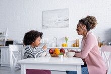 Side View Of African American Mom And Daughter Looking At Each Other During Breakfast