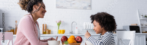 Photo happy african american mom and daughter looking at each other during breakfast,