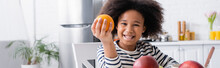 African American Child Smiling At Camera While Holding Ripe Orange, Banner