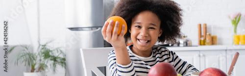 Fotografie, Tablou african american child smiling at camera while holding ripe orange, banner