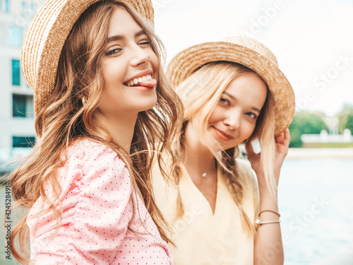 Photo Two young beautiful smiling hipster woman in trendy summer sundress