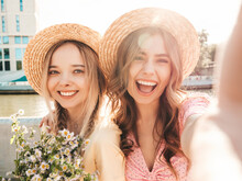 Two Young Beautiful Smiling Hipster Woman In Trendy Summer Sundress. Sexy Carefree Women Posing On The Street Background In Hats. Positive Models At Embankment At Sunset. Taking Selfie.Holding Flowers