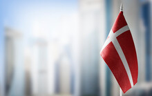 A Small Flag Of Denmark On The Background Of A Blurred Background