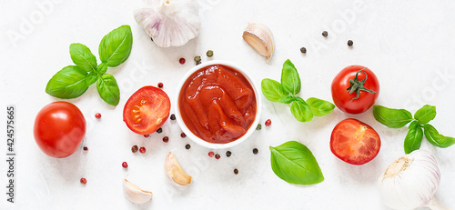 Fototapeta Long wide banner with homemade tomato sauce with fresh aromatic basil, cherry tomatoes, peppercorn and garlic on white marble background. Culinary blog banner concept. obraz