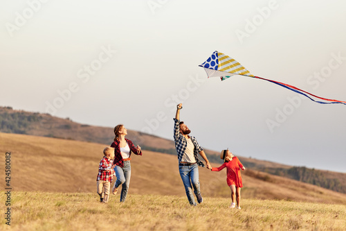 Obraz Happy family father,  mother and children launch  kite on nature at sunset - fototapety do salonu