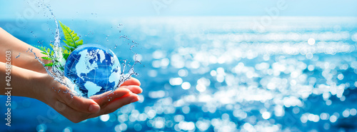 Fototapeta Environment Concept - Hands Holding Globe Glass In Blue Ocean With Defocused Lights obraz