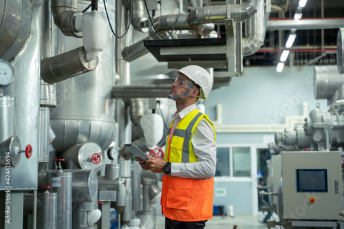 Obraz na plátně Engineer checking and maintenance technical data of system equipment condenser Water pump and piping air compressor system at manufacturing factory