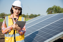 Asian Woman Workers Technicians Using Tablet And Control Installing Heavy Solar Photo Voltaic Panels To High Steel Platform In Corn Field. Photovoltaic Module Idea For Clean Energy.