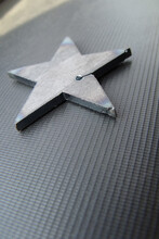 Star-shaped Steel Laser Cutting Scrap.  Steel Scraps In The Shape Of A Star Left After Laser Cutting Of Metal. Close Up Photo, Blurred Gray Background. Vertical Format.