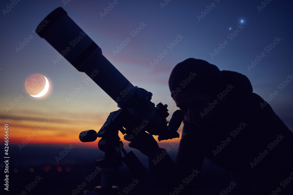 Fototapeta Woman looking at night sky with amateur astronomical telescope.