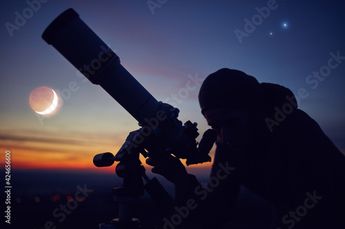 Obraz Woman looking at night sky with amateur astronomical telescope. - fototapety do salonu