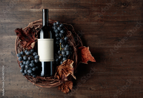 Fototapeta Bottle of red wine with grapes and dried vine leaves on an old wooden background. obraz na płótnie